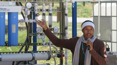 Dine College Student Larry Moore demonstrates the water filtration unit on Navajo Nation